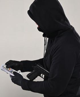 Mann in schwarzer maske und kapuzenpulli mit einer pistole und einer packung dollar auf grauem hintergrund