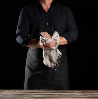 Mann in schwarzer uniform hält grauen leinenlappen und wischt seine hände über leeren holztisch, schwarzen hintergrund, koch
