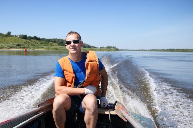 Mann in schwimmweste auf dem boot bewegt sich schnell