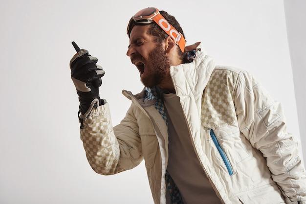 Mann in snowboardausrüstung mit brille auf dem kopf, der in walkie-talkie schreit