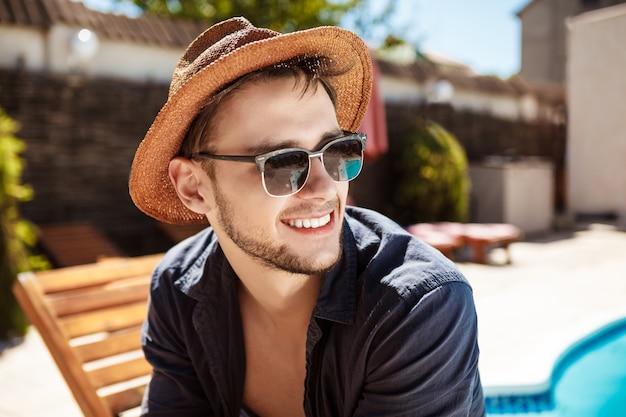 Mann in sonnenbrille und hut lächelnd, in der nähe von schwimmbad sitzend