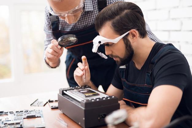 Mann in spezialbrille hält einen schraubenzieher in der hand.