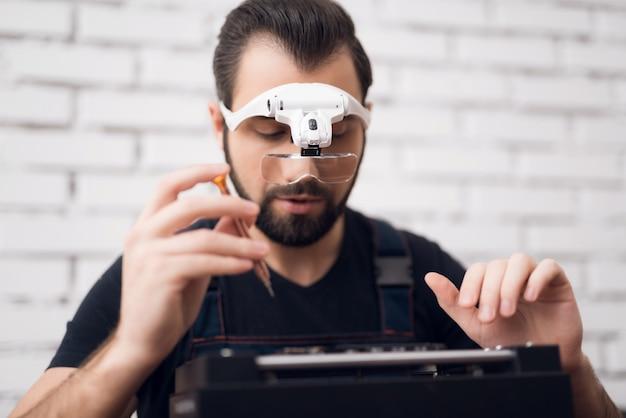 Mann in speziellen gläsern hält einen schraubenzieher in seiner hand.