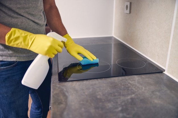 Mann in spezieller gelber kleidung mit einem spray und gummi, um schmutz von einem ofen zu entfernen