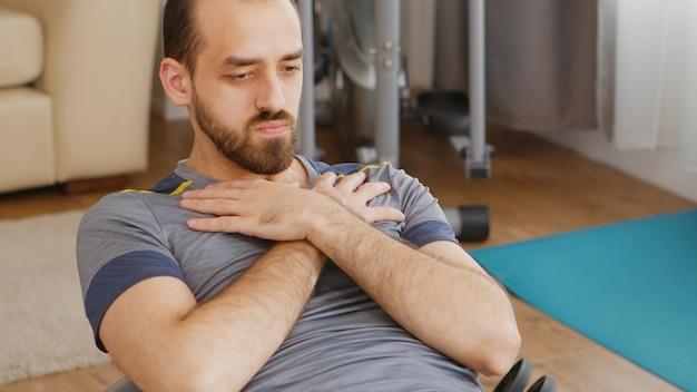 Mann in sportbekleidung trainiert bauchmuskeln auf schweizer ball im wohnzimmer.