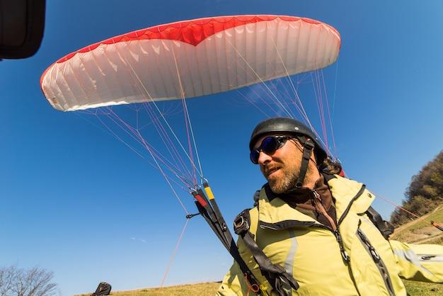 Mann in touristischer kleidung, der auf einem fallschirm fliegt, natur, blauer himmel