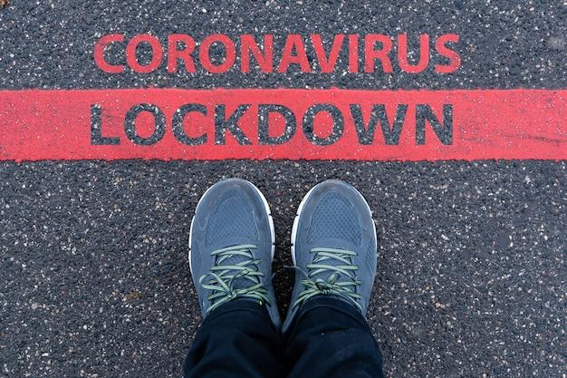 Mann in turnschuhen, die neben einer roten linie mit text coronavirus lockdown, einschränkung oder sicherheitswarnkonzept stehen