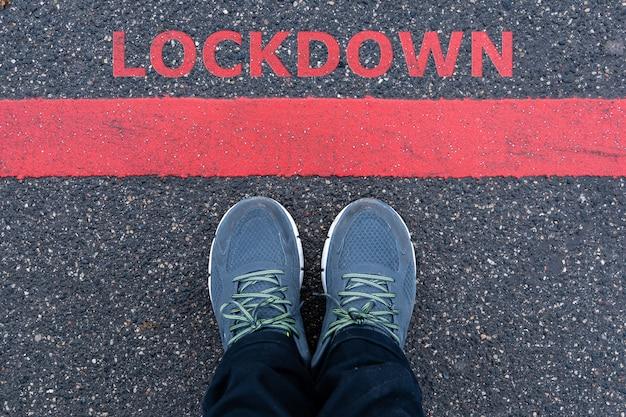 Mann in turnschuhen, die neben einer roten linie mit text lockdown, einschränkung oder sicherheitswarnkonzept stehen