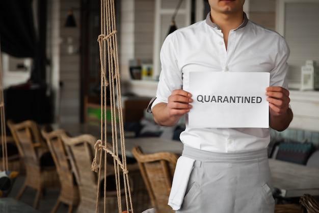 Mann in uniform hält weißes blatt papier mit wort quarantäne