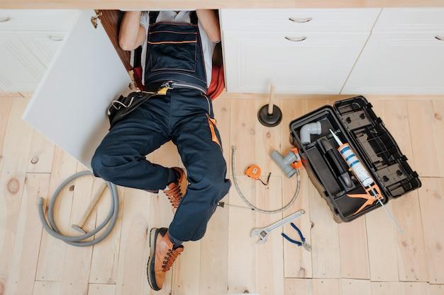 Mann in uniformarbeit in der küche unter der spüle