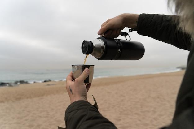 Mann in warmer jacke mit hand-tätowierungen, gießt heißen kaffee oder tee in thermosisolierte tasse an kaltem regnerischem tag.