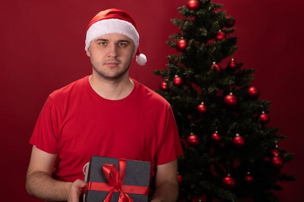 Mann in weihnachtsmannmütze und rotem t-shirt hält geschenkbox mit weihnachtsgeschenk