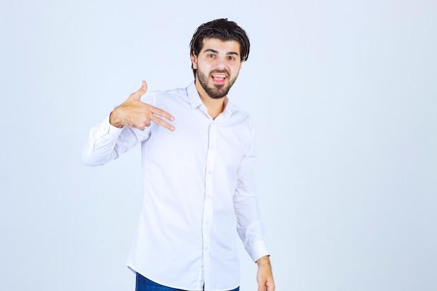 Mann in weißem hemd, der auf sich selbst zeigt.