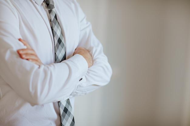 Mann in weißem hemd und grauer, karierter krawatte posiert die hände im weißen raum gekreuzt