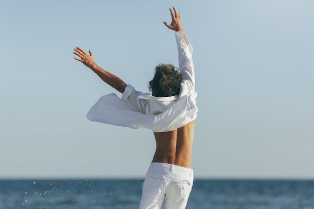 Mann in weißem hemd und hose hebt seine hände am strand