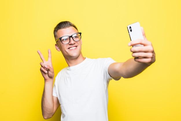 Mann in weißem t-shirt und brille macht etwas auf seinem handy und macht selfie-bilder siegeszeichen