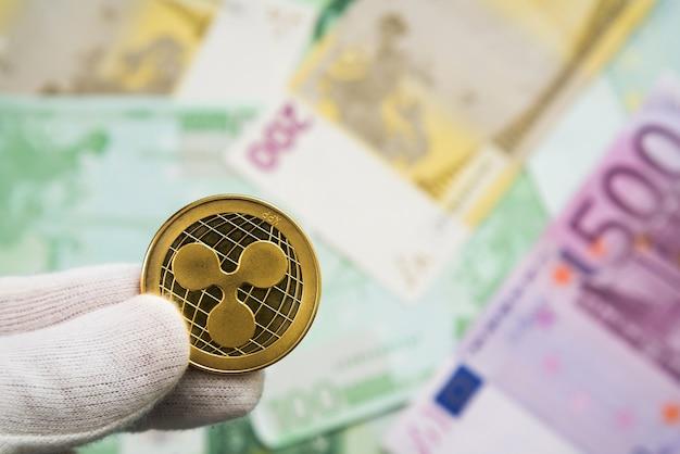 Mann in weißen nelken, die ripple-münze zwischen den fingern mit euro-noten in der oberfläche halten.
