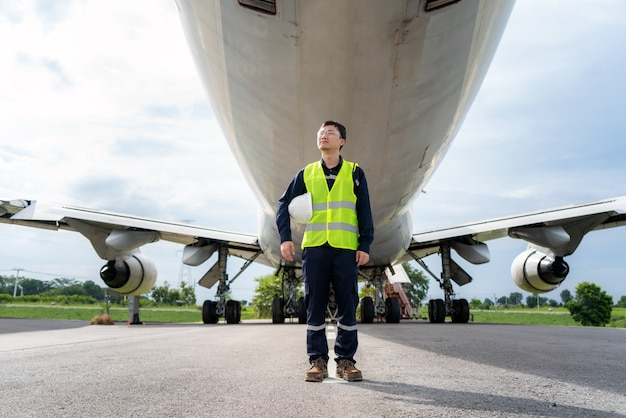 Mann ingenieur wartungsflugzeug hält weißen helm im vorderen flugzeug von reparaturen