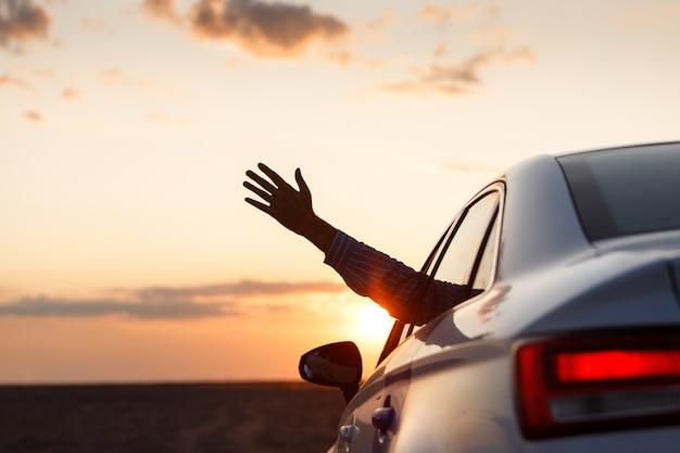 Mann innerhalb des autos, das seine hand im freien zeigt / aus autofenster bei sonnenuntergang heraus sich lehnt