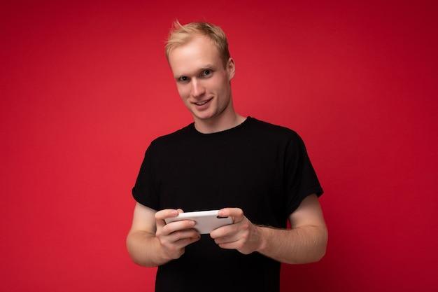 Mann isoliert über rote wand, die schwarzes t-shirt hält, das handy hält und sms schreibt.