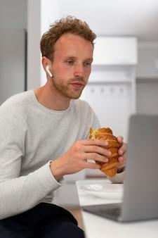 Mann isst croissant mittlerer schuss