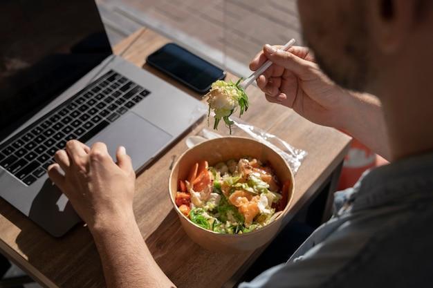 Mann isst essen zum mitnehmen und benutzt laptop