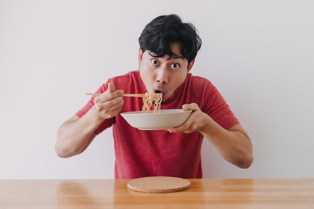 Mann isst instantnudeln sehr lecker