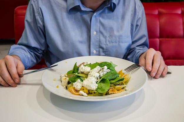 Mann isst salat, während er an einem tisch in einem restaurant sitzt. männliche hände hautnah am tisch
