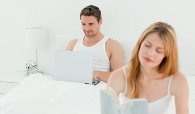 Mann ist auf seinem laptop, während seine frau ein buch liest