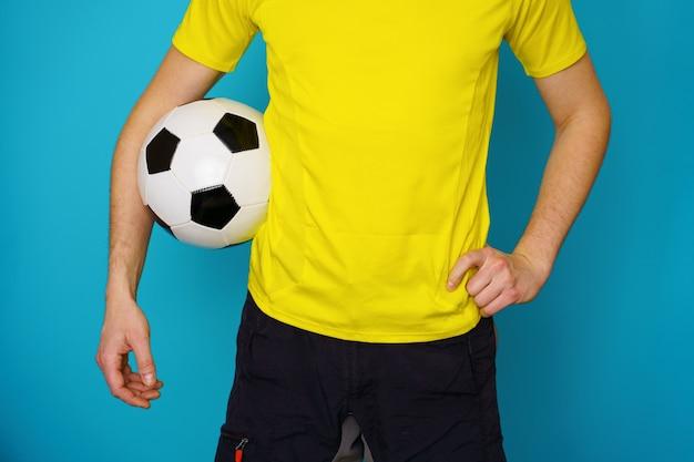 Mann ist fußballfan in gelbem t-shirt mit fußball auf blauem hintergrund