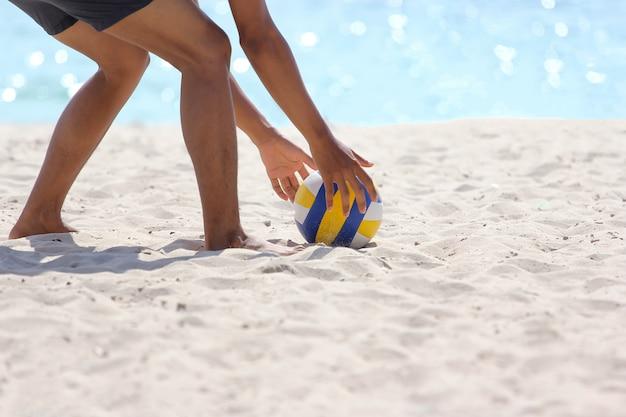 Mann ist gebeugt, wählen sie den volleyball auf meersand
