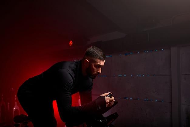 Mann ist in einem heimtrainer beschäftigt, persönliches training im rot neonbeleuchteten fitnessstudio, trainingsanzug tragend