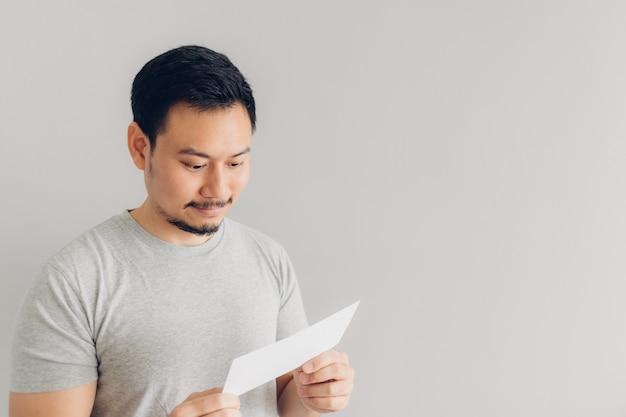 Mann ist mit der weißen postnachricht oder der rechnung glücklich.