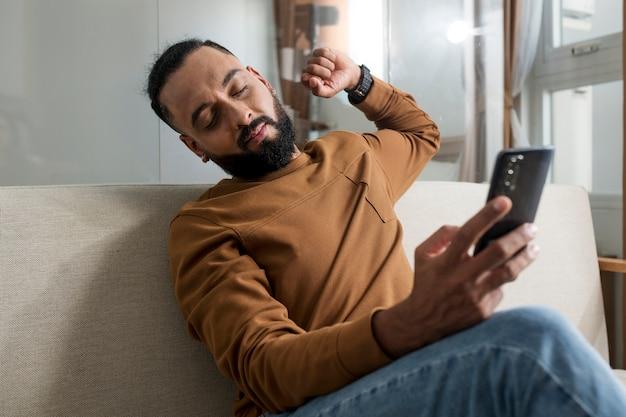 Mann ist müde, nachdem er zeit mit seinem smartphone verbracht hat
