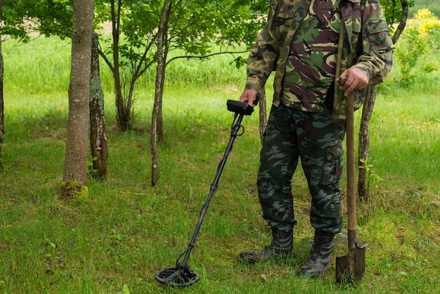 Mann jagt schatz mit metalldetektor im herbstwald