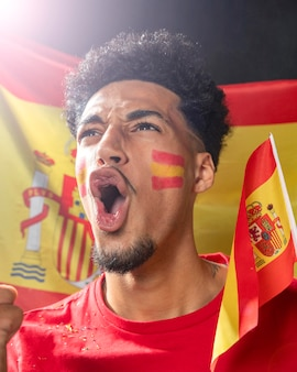 Mann jubelt und hält die spanische flagge