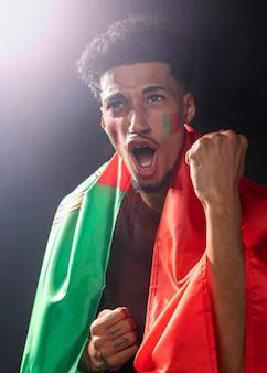 Mann jubelt und trägt die portugiesische flagge