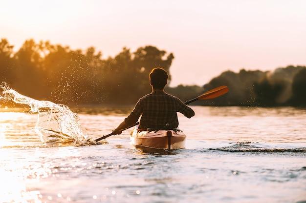 Mann kajakfahren. rückansicht des jungen mannes, der wasser beim kajakfahren auf dem fluss mit sonnenuntergang im hintergrund spritzt