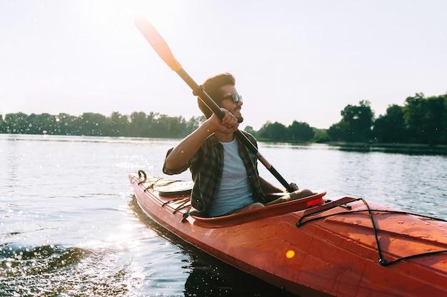 Mann kajakfahren. schöner junger mann, der auf dem see kajak fährt und lächelt