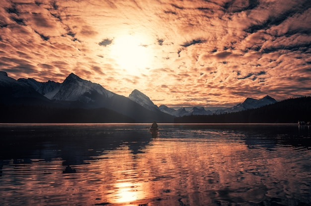 Mann kanufahren mit kanadischen rocky mountains und bunt bewölkt auf maligne see am jasper nationalpark