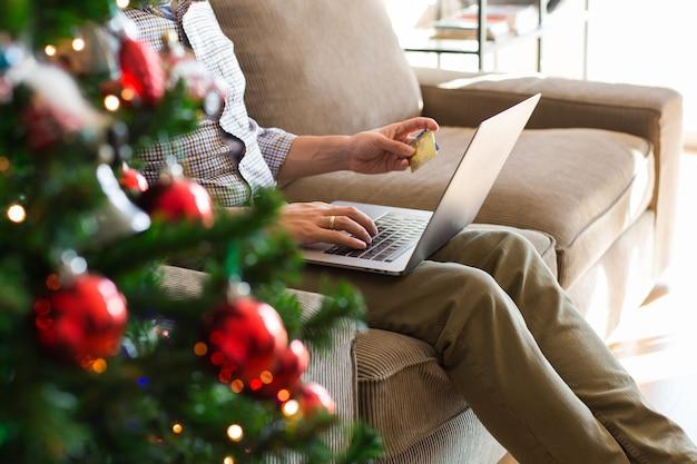 Mann kauft weihnachtsgeschenke für das neue jahr online mit telefon-laptop