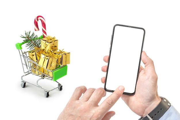 Mann kauft weihnachtsgeschenke unter verwendung des telefons mit leerem weißen bildschirm.