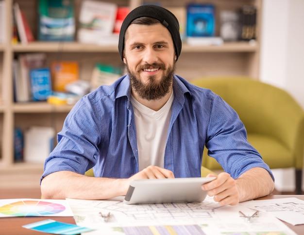 Mann kleidete das zufällige sitzen bei tisch und die anwendung der digitalen tablette