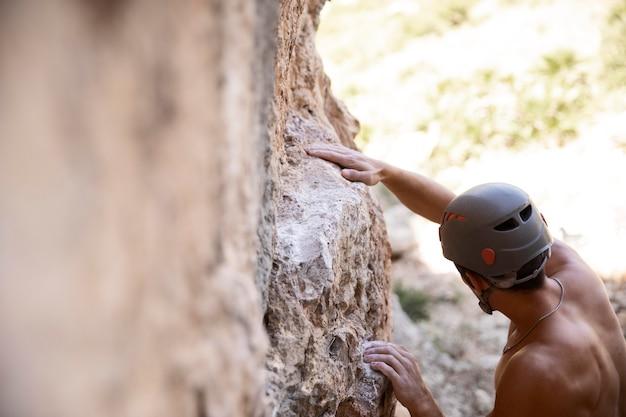 Mann klettert auf einen berg mit sicherheitsausrüstung