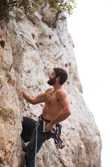 Mann klettert mit spezialausrüstung