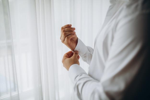 Mann knöpft hemd, ein mann in einem weißen hemd, hände eines mannes nahaufnahme, geschäftsmann zieht einen anzug an