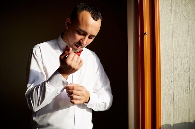 Mann knöpft sein weißes hemd, das vor einem hellen fenster steht