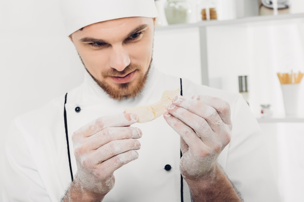Mann koch in uniform macht kekse mit backformen