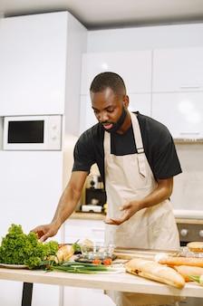 Mann kochen. afroamerikanischer mann, der in einer küche bleibt. mann im schwarzen t-shirt.