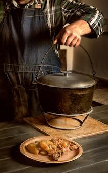 Mann kocht braten. eine portion braten auf einem teller, der koch hebt einen gusseisernen topf